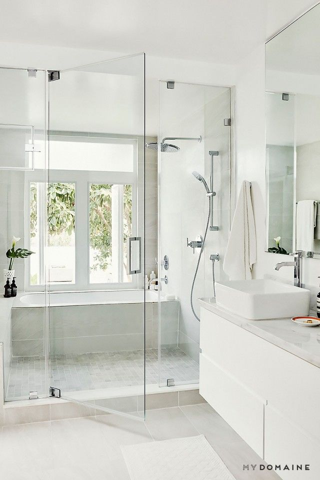 A modern bathroom with a large shower, a bathtub, and a floating sink