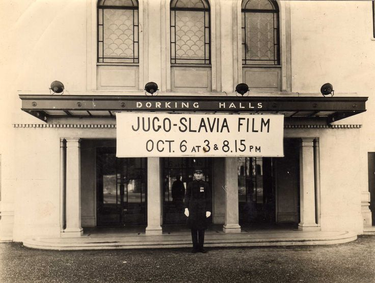 """Brian Buss's father was the first caretaker at Dorking Halls: """"I vividly remember coming to live at the Halls when only four and moved out after I married in 1949. This photo is of my father standing outside of the main entrance in the very early 1930s before a function. He is in his smart commissionaire's uniform he was issued with along with his white gloves and his WW1 medals. As children we always knew of his approach by the noise they made hitting one another."""""""