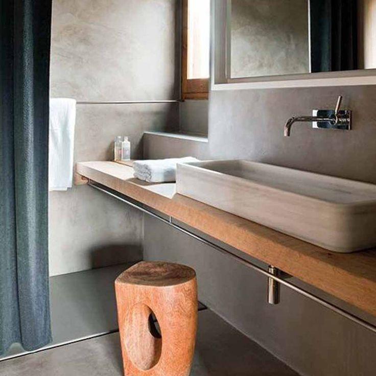 Bagno con pavimento e rivestimento in cemento, lavabo da appoggio su base in legno e sgabello