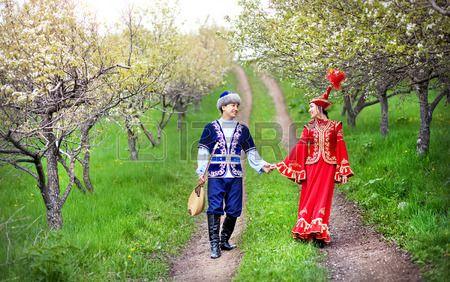 Pareja en traje de Kazajst n a pie por la primavera floreciente jard n de la manzana de Almaty Kazaj Foto de archivo