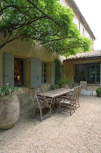 European farmhouse or French farmhouse courtyard with rustic dining table and chairs. #frenchfarmhouse #europeanfarmhouse #exterior #courtyard #dining
