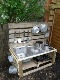 Simple mud kitchen with an old sink and aluminum pans
