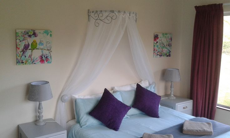 Cottage bedroom with wrought iron half tester over the bed