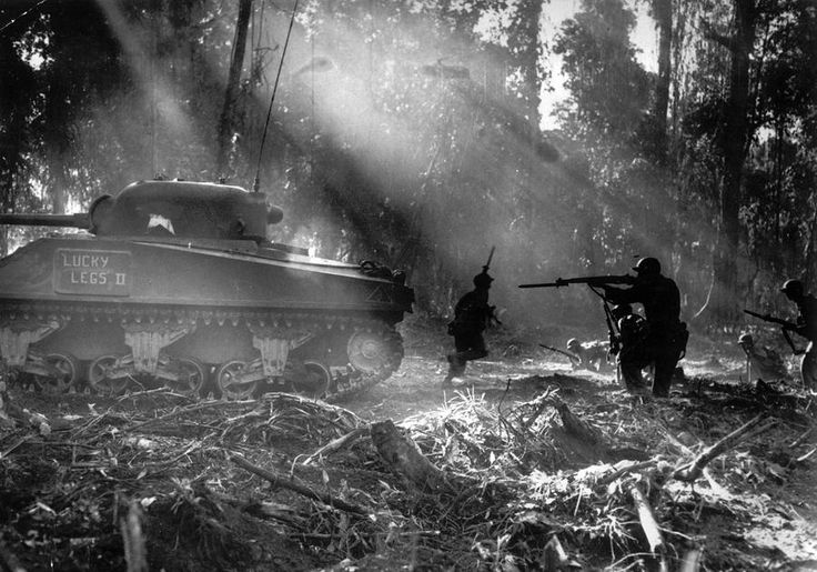 Following in the cover of a tank, American infantrymen secure an area on Bougainville, Solomon Islands, in March 1944, after Japanese forces infiltrated their lines during the night.