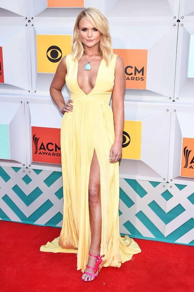 Miranda Lambert is wearing a pale yellow Christian Siriano dress with a plunging neckline and slit. Miranda is beautiful in this dress! The color is perfect for spring! I love the pop of pink with the Joyce Echols heels and the necklace.