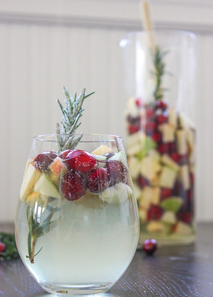 Recipe: Cranberry & Rosemary White Sangria Ingredients: 2 apples, granny smith and a braeburn 1 heaping cup of fresh cranberries 1 large sprig of fresh rosemary, extra for garnish 1 bottle of Pinot Grigio 1/2 cup of white grape juice 1/4 cup of sugar, more for garnish 1 can of club soda