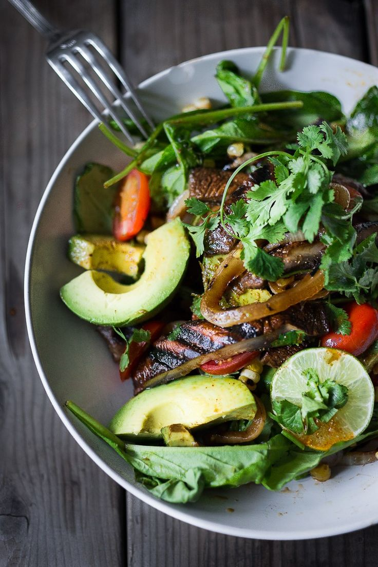 A simple tasty recipe for Grilled Portobello Steak Salad with avocado, lime, grilled sweet onions, grilled corn, tomatoes and a Smokey Lime Dressing. Vegan and Gluten Free!   www.feastingathome.com