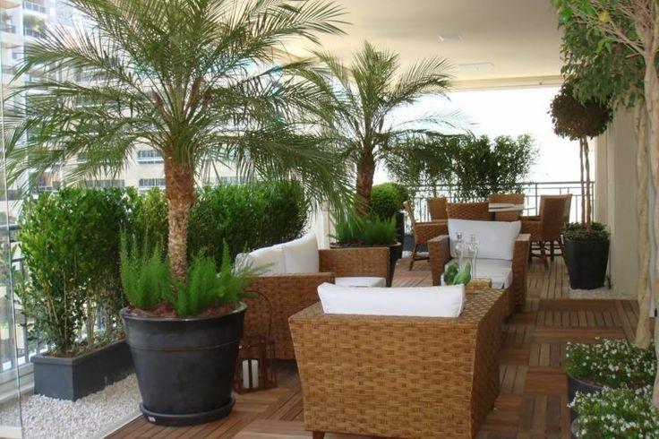 balcon avec mobilier en rotin et palmiers en grandes jardinières
