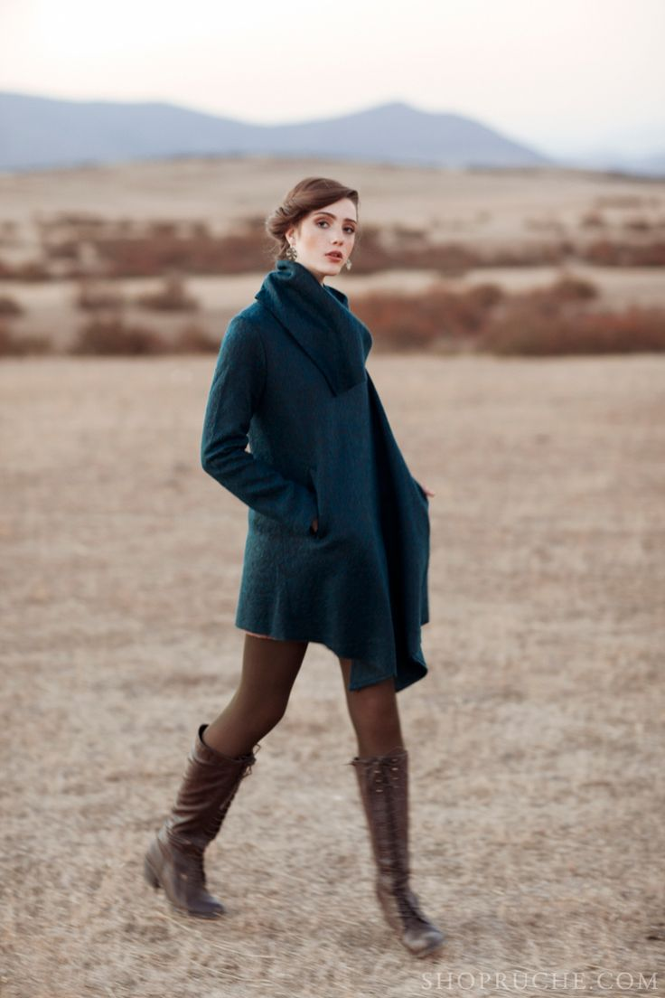 A rich teal coat paired with brown tights and laced up riding boots.