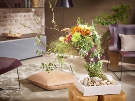"""Herbstlicher Blütenstrauß Autumn Breeze Diese wie natürlich verweht erscheinenden Sträuße in aktueller Bundle-Optik begleiten uns durch den Herbst. Mit ihrer asymmetrischen Form, ihrer herbstlichen Blütenfülle und ihrem unempfindlich-robusten Look sind diese herb nach Salbei und Rosmarin duftenden """"Naturburschen"""" echte Eyecatcher. In der schlichten Naturstein-Schale erhält dieses Blumenarrangement einen besonderen Kick durch die Taillierung mit einem robusten Ledergürtel."""