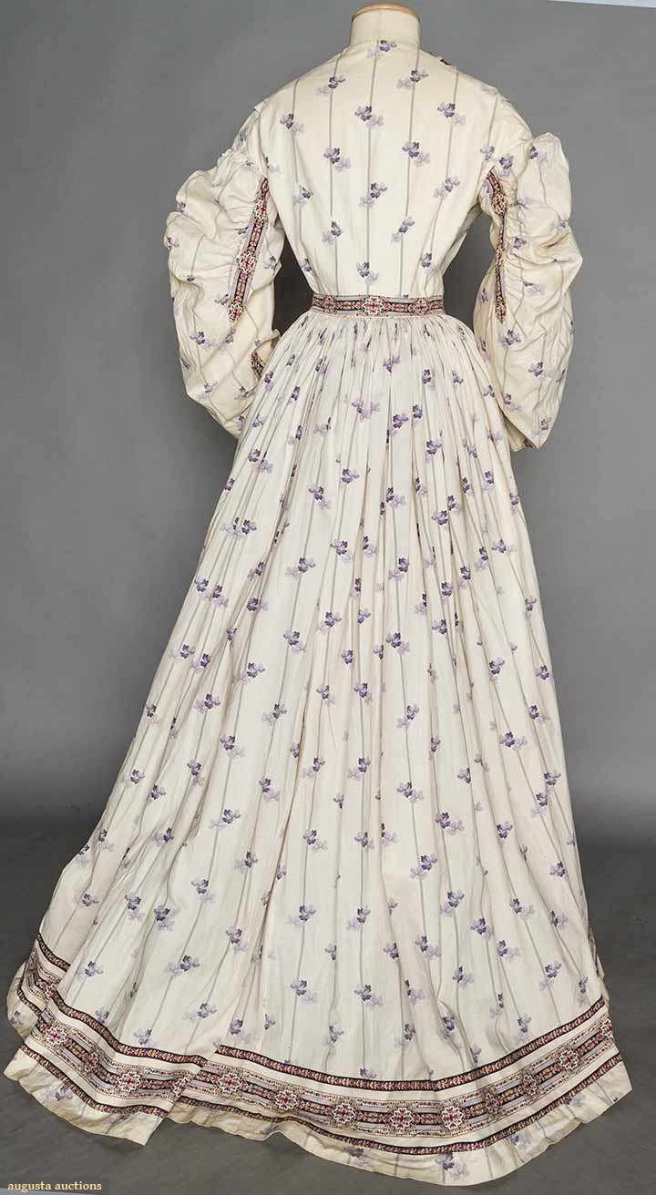"""1860s purple maternity dress. Pale purple leaves & stripes on white cotton, border trim bands of geometric & floral print, ruched & banded sleeves, W seam on sides & back, 2 F panels w/o seams, 38 F buttons, B 32"""", W to 40"""", L 55""""-61"""". Pocket set in seam."""