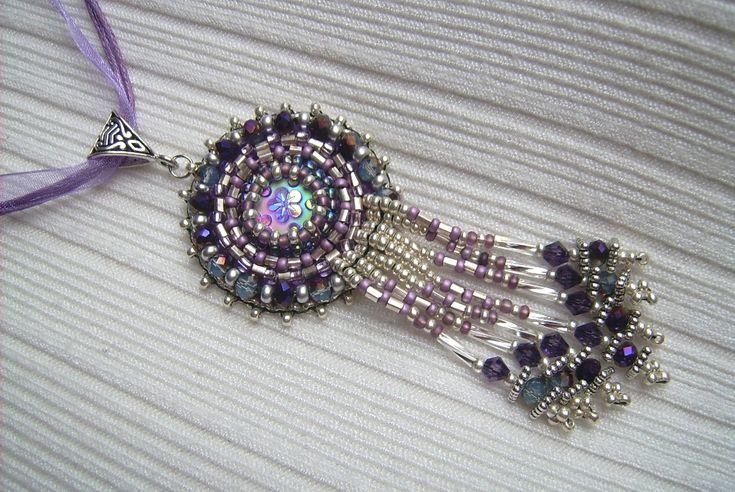 Ny-552. Lila és ezüst színű, csüngős, gyöngy-hímzett medál, lila színű organza szalagon. Ára: 1300.-Ft.