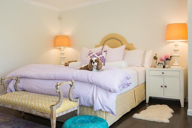 Lovely purple and gold bedroom bedroom boast white cabinet nightstands topped with tall white and gold lamps accented with gold lamp shades and located on either side of a gold arch headboard.