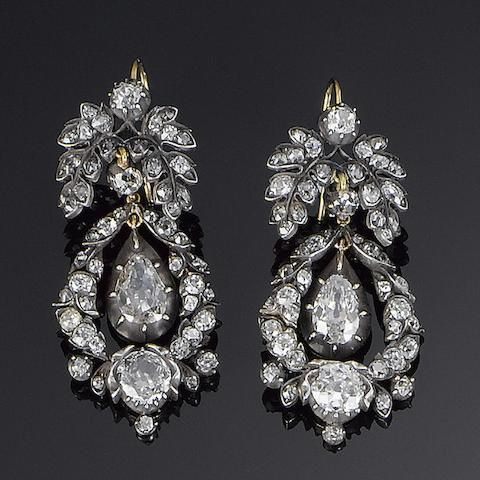 A pair of 19th century diamond pendent earrings Each old brilliant-cut diamond foliate surmount suspending a similarly set stylised garland with a pear-shaped diamond swing centre, mounted in silver and gold