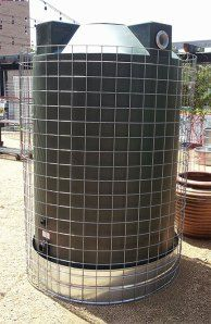 How to hide a rain collection tank with vines, roses or ivy!  Use ranch wire to create a trellis to cover a not so pretty rain harvesting tank.