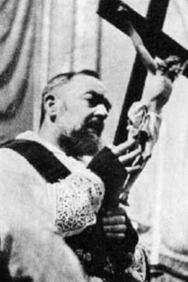 Padre Pio venerates The Cross.
