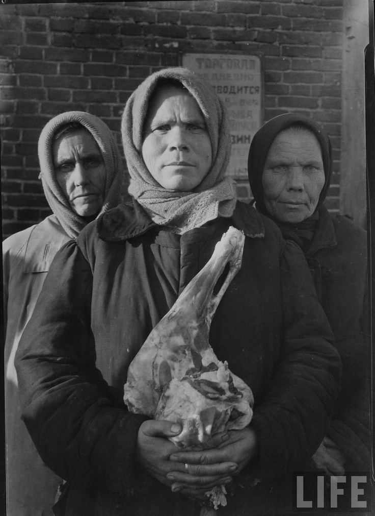 Russian woman grimly holding a slab of meat, Magnitogorsk, 1931 by Margaret Bourke-White