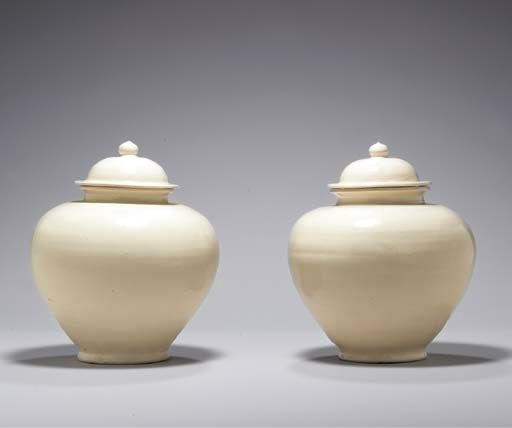 A rare pair of glazed white ware jars and covers, Tang dynasty (618-907)