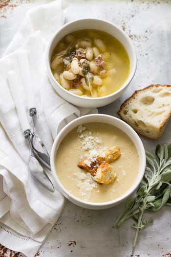 """これはぜひ試してもらいたいポタージュです。  """"2way""""というのは、ホクホクとした豆の美味しさを味わうスープを作り、半分はそのままで楽しみ、残りの半分をブレンダー等ですり潰して、ポタージュにするというのものです。  【材料】乾燥白いんげん豆450g・ベーコン1,2枚・さいの目に切った玉ねぎ1個とセロリ1本・スライスしたニンニク2片・セージの葉4枚(なければ省略)・チキンスープ2L・オリーブオイル小さじ1・塩,胡椒 ◇飾り付け:ガーリッククルトン・パルメザンチーズ"""