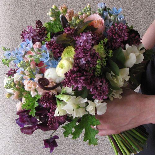 just picked bridal bouquet with uluhe fern shoots, deep purple sweet peas, plum ranunculus, lilacs, tweedia, scented geranium, alchemilla, cream ranunculus, ivory sweet peas, peach stock, and peach ranunculus, for a ceremony in Phoenix, Arizona