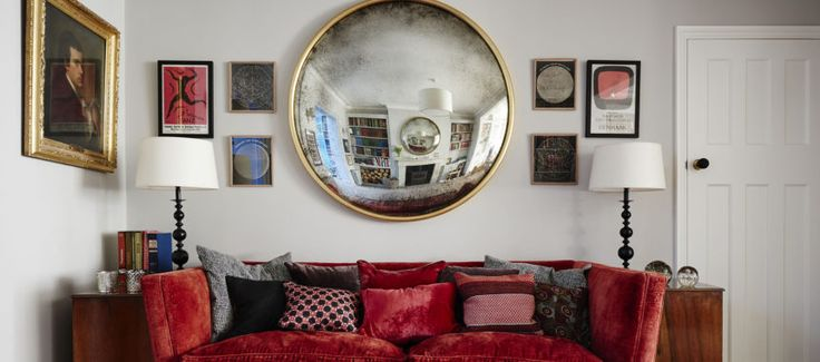 English living room with large convex mirror over couch at centre of gallery wall, mix of vintage furniture and lamps , art