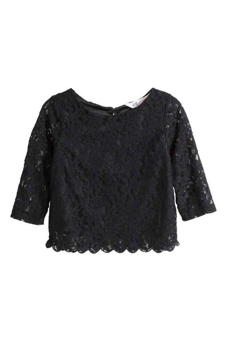 Kanten bloes: Een licht uitlopende bloes van kant. De bloes heeft driekwart mouwen, een splitje met een knoop in de nek en een voering van tricot.