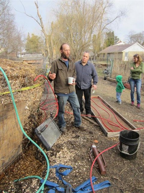 Explaining the compost furnace and how it will heat a greenhouse in the spring.