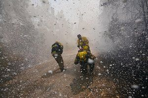 Firefighters protect themselves from foam discharged from a plane attempting to extinguish a forest fire in Concepción