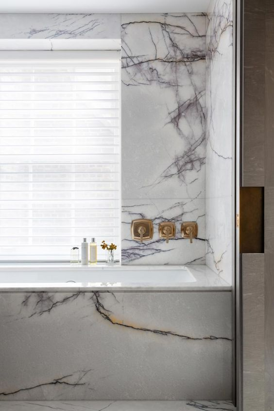 A Black And White Marble Bathroom With White Window Shadings And Warm Brass F