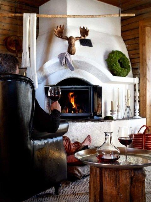 El otoño es mucho más delicioso frente a una chimenea. Las casas rústicas exprimen todo su potencial con elementos a su alrededor que lo ensalzan: coronas de hoja verde, cabezas de animales y mobiliario de madera noble para un cálido relax. Foto: Affari