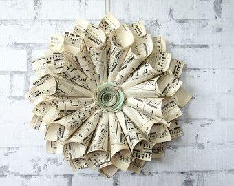 Deze krans is gemaakt van de paginas van de antieke (circa 1930) muziekboeken. Het maatregelen aprox 12-13 inch in diameter. Het centrum is een roos met bladmuziek en kraft cardstock handgeschept papier. De achterkant is net zo schoon op zoek als de voorkant, dus dit stuk kan worden geplaatst op een glazen deur of mirror. Het wordt gehangen met een lange bindgaren lint en zou ziet er mooi op de muur in uw home bibliotheek of zelfs op de deuren van de ingang van uw muziek thema bruiloft! Elke…