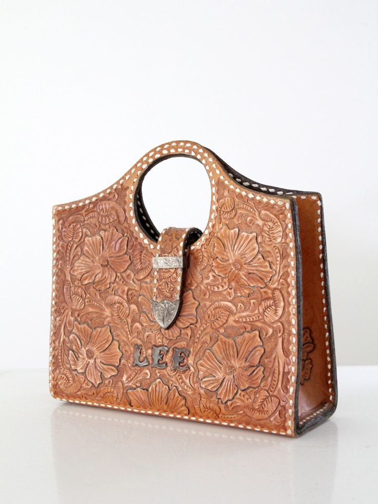 "vintage tooled leather tote bag 1950s - Thick, caramel brown leather bag - Western style tooled floral design - Silver tone metal fixtures - Belt strap fold over ""closure"" - ""LEE"" in etched silver let                                                                                                                                                                                 More"