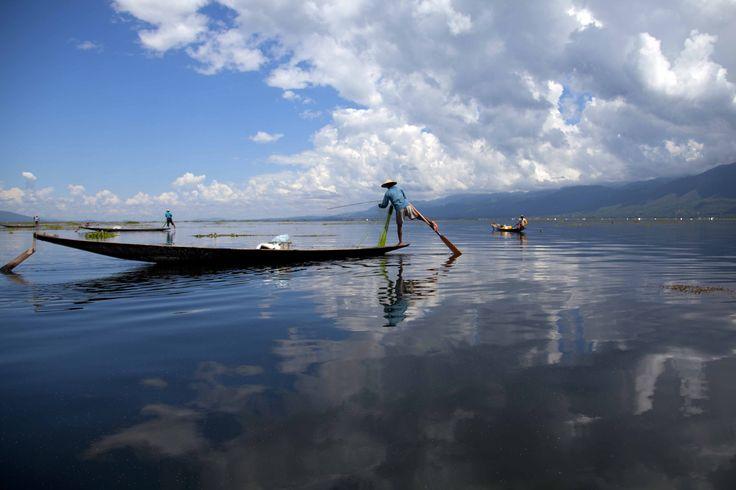 Warga suku Innthas menggunakan perahunya untuk menangkap ikan di Danau Inlay, Nyaung Shwe, Myanmar selatan.