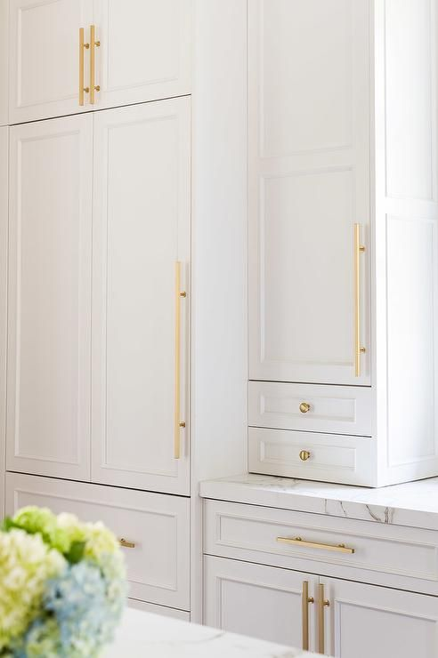 White cabinets adorned with long brass pulls and brass knobs paired with Silestone quartz countertops.