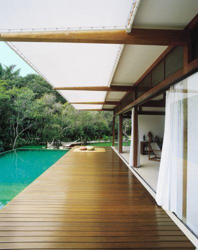 A varanda/deck que integra piscina e o living da casa é protegida pelo toldo de poliéster branco microperfurado. Ao fundo, o espaço para as redes pertence ao jardim e desfruta da proximidade da área de preservação ambiental