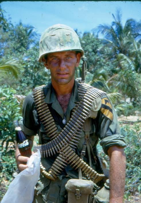 A soldier with no helmet band and a full color divisional patch advertises a Coke bottle while carrying several belts of 7.62 ammunition.
