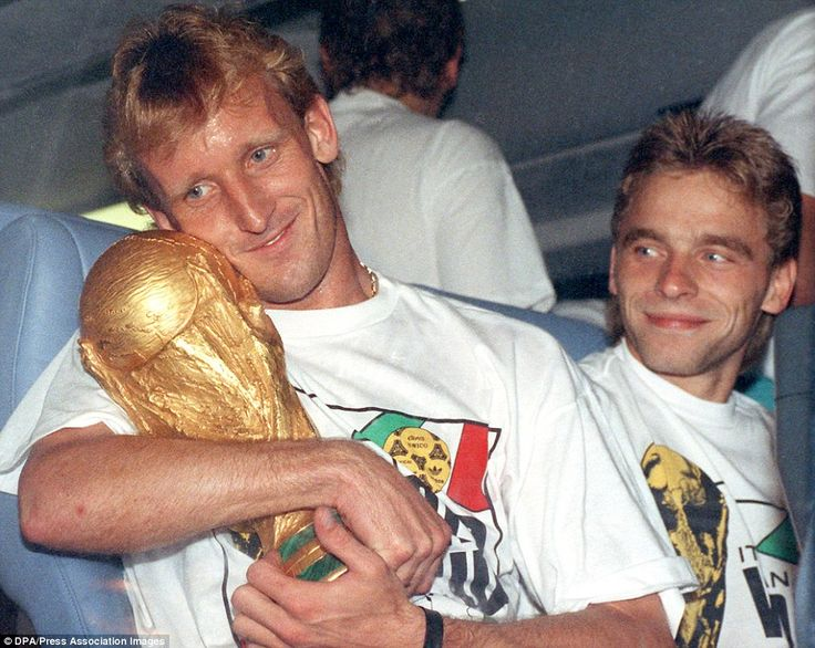 West Germany defender Andreas Brehme holds the World Cup trophy in his arms as the German team bus leaves Rome's Olympic Stadium in 1990. Brehme's late penalty against Argentina gave the Germans a 1-0 win in the final, their third World Cup triumph