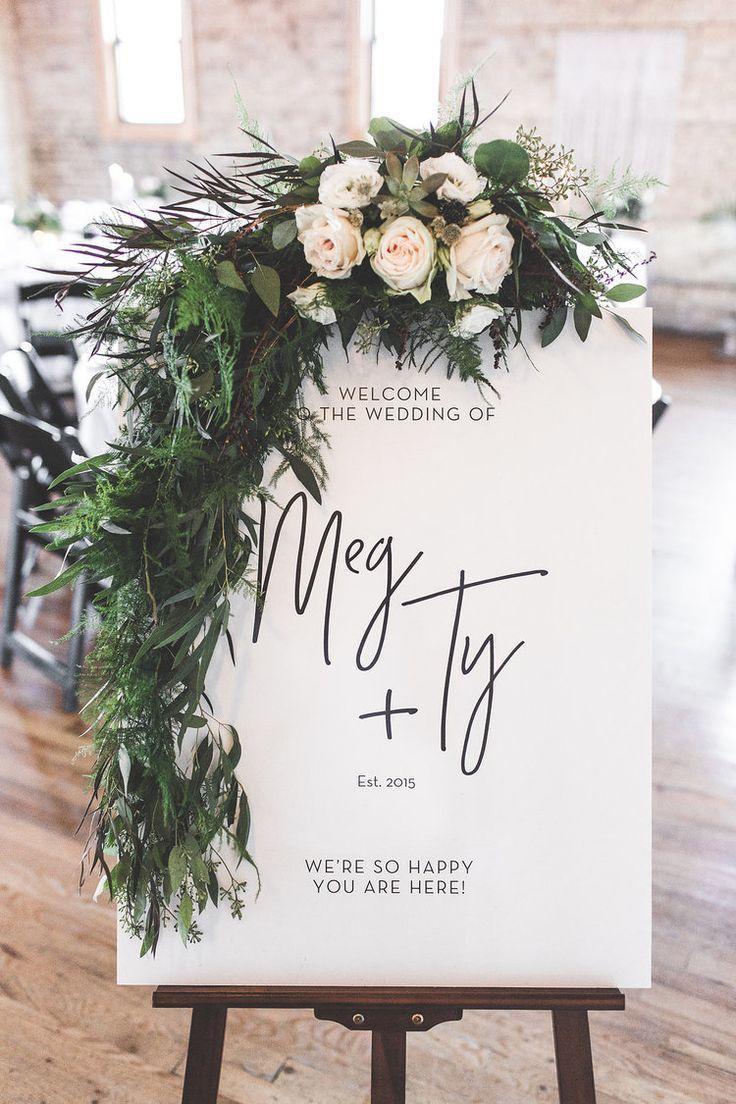 Hochzeit Willkommensschild auf einer Staffelei mit einem großen grünen Kranz überlagert