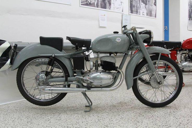 Vůbec prvním motocyklem DEMM byla tahle dvoutaktní 125ccm Turismo, vyrobená v roce 1953. Vzhledem k následujícím modelům je lakovaná dost nudnou šedou barvou, což mělo ale svůj velmi významný důvod. Do té doby továrna vyráběla jen obráběcí stroje. Měly dobrou pověst u zákazníků a aby tuto pověst přenesly i na své nové motocykly, nalakovali první modely naprostou stejnou barvou, jakou lakovali své soustruhy a frázy. Fotka uživatele Jihočeské motocyklové museum.