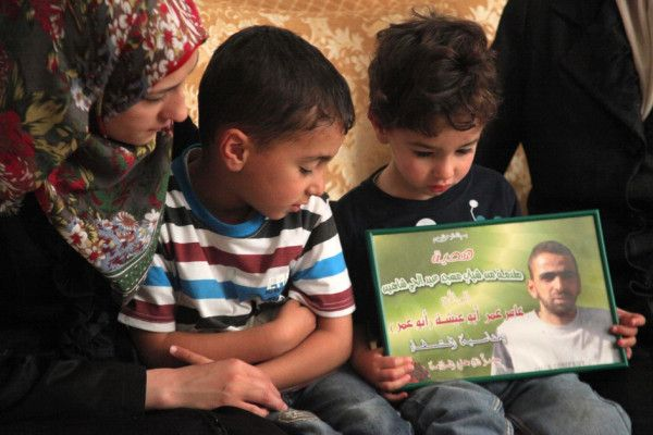 The son of Amer Abu Eishe holds his father's picture as he poses with his brother and his mother for media in their house in the West Bank city of Hebron, 27 June. Israel named Abu Eishe as one of two men it suspects are behind the 12 June disappearance of three Israeli teenagers in the occupied West Bank. The teens' bodies were found near Hebron on 30 June.