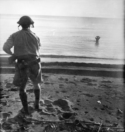 Japanese soldier about to commit suicide with a grenade against his head while an Australian soldier watches (New Guinea, December 18, 1942)