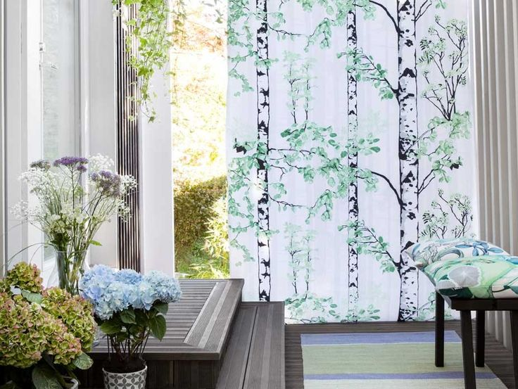 Luontopolku Curtain Panel features a nature trail full of birch trees. The tree trunks pictured from different distances create depth of space in the pattern and the green hues keep the atmosphere fresh and peaceful.