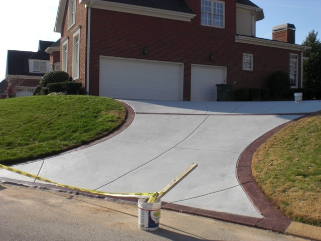 The Driveway Has A Solid Stain In Silver Gray With A Semi