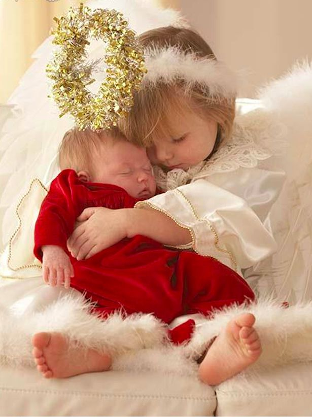 Sweet little angel hugs baby sister • photo: Ariel Skelley on Getty Images