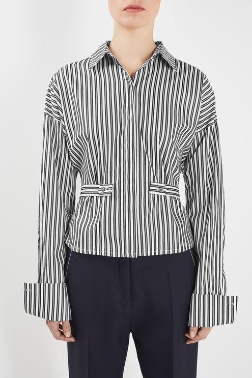 The Tiller Shirt features novel tailoring with dropped shoulders and adjustable side tabs that cinch the waistline for a feminine fit. This concealed button-up in black and white striped cotton is finished with oversized cuffs and punctuated by mother of pearl detail buttons.