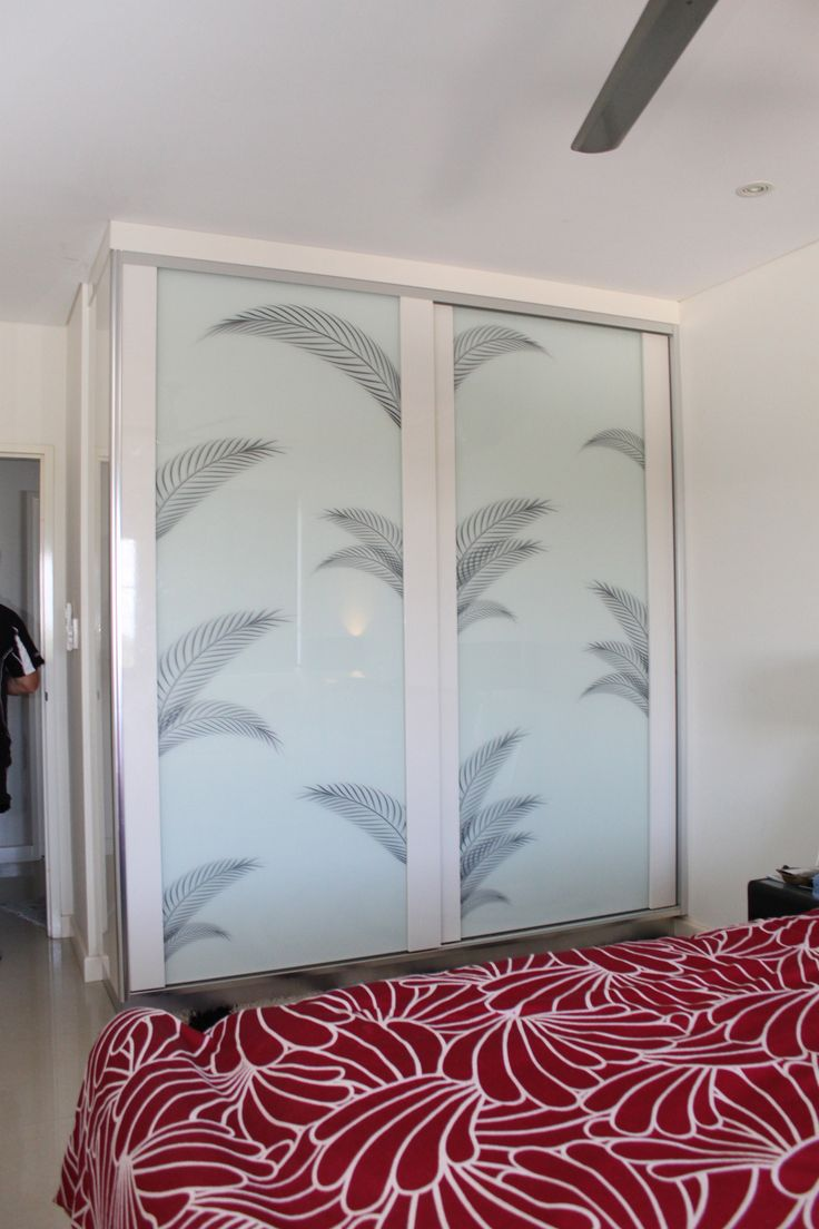 Sliding Infinity Doors with painted white timber frames.  White glass with palm frond motifs. www.formfunctionnt.com.au