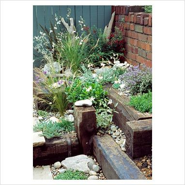 Seaside themed border - driftwood, shells & railway sleepers.
