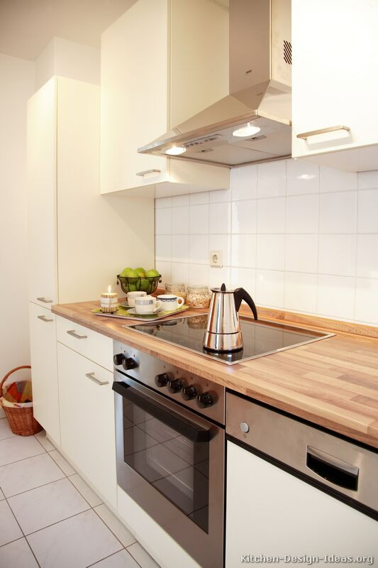 Small #Kitchen Idea of the Day: White cabinets and tile with light wood-grain laminate countertops keep a small space feeling bright.