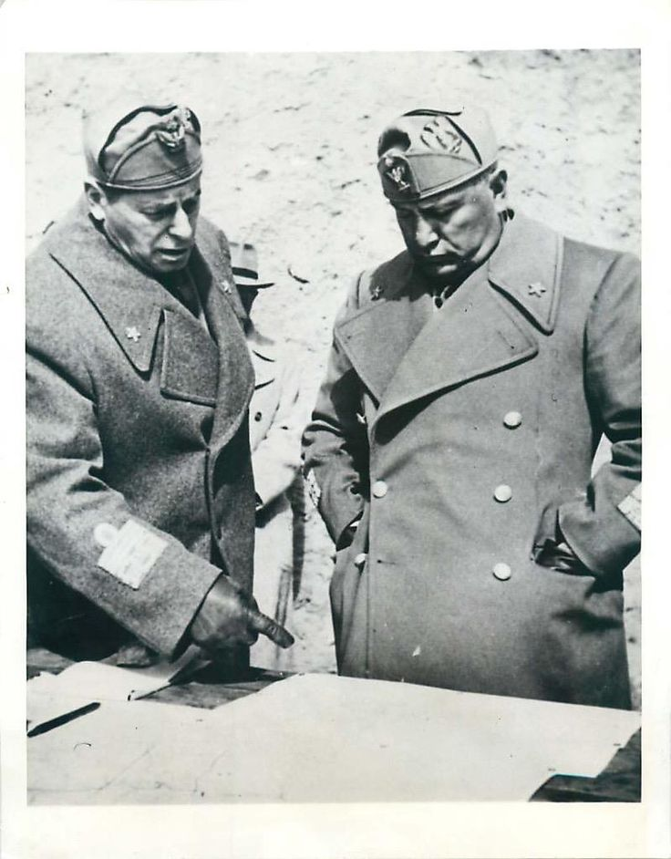 1941- Premier Benito Mussolini looks on as staff officer points out a planned offensive on a war map at the Greek front.