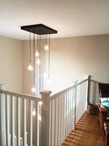 Staggared Pendant Light Reclaimed Wood Chandelier over a staircase.